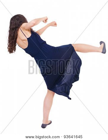 curly woman funny fights waving his arms and legs. Isolated over white background. Girl in a blue evening dress fights feet.