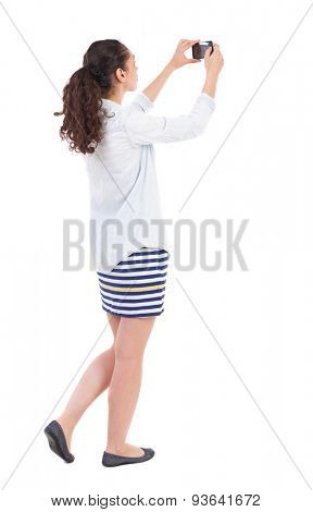 back view of standing curly woman with mobile phone in the hands of. girl  watching. Rear view people collection.   Isolated over white background.  African-American woman doing self phone