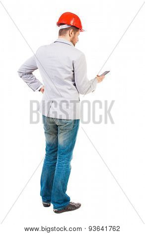 Backview of business man in construction helmet stands and enjoys tablet or using a mobile phone. Standing young guy. Isolated over white background.  Managing working at a construction site on phone