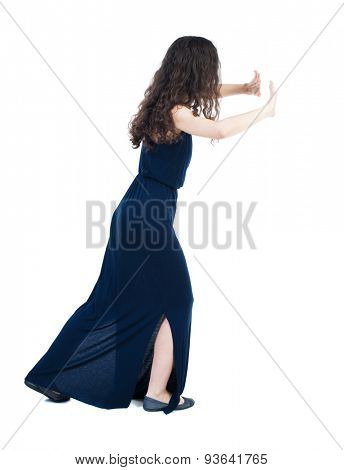 back view of woman pushes wall. Isolated over white background. Rear view people collection. backside view of person.  Girl in a blue evening dress is pushing the right wall.