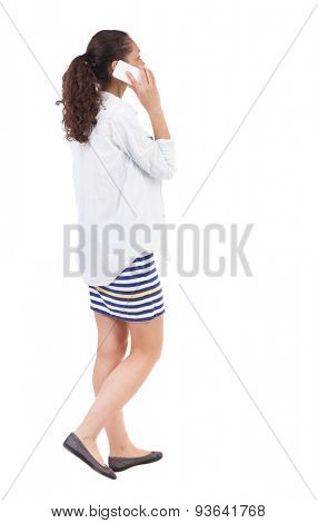 a side view of a woman walking with a mobile phone. beautiful curly girl in motion.  backside view of person.  African-African-American woman on the move enthusiastically talking on the phone