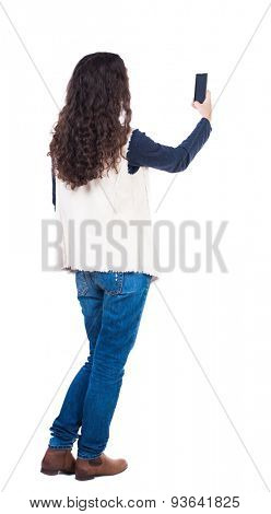 back view of standing young beautiful  woman and using a mobile phone. girl  watching. Rear view people collection.   Girl with long curly hair photographed on the phone.