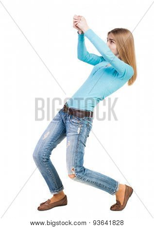 back view of standing girl pulling a rope from the top or cling to something.  backside view of person.  Isolated over white background. Strongly leaning back, she pulls the top rope.