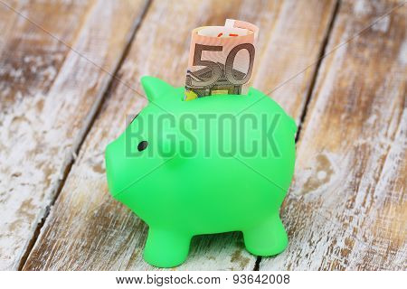 Piggy bank with banknote sticking out of it