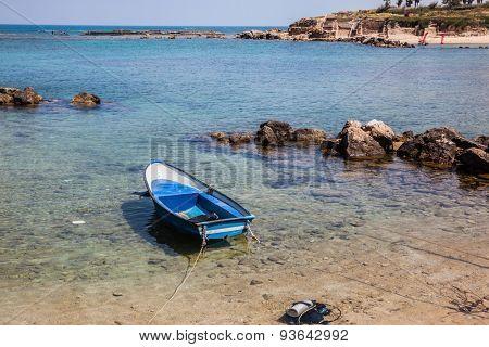 The shallow bay and blue fishing boat, moored near the shore. Next to the boat - diving equipment