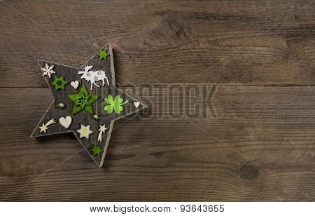 Christmas background with a handmade star of wood and green decoration.