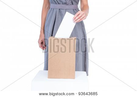 Businesswoman putting ballot in vote box on white background