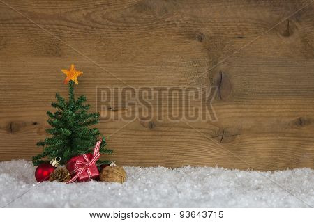 Christmas tree with presents on a wooden background with snow.