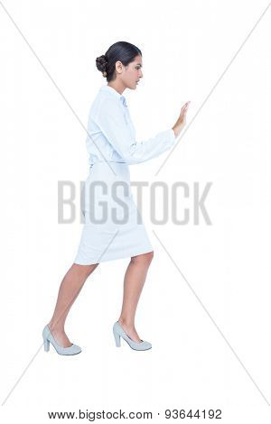 Businesswoman standing and pushing on white background