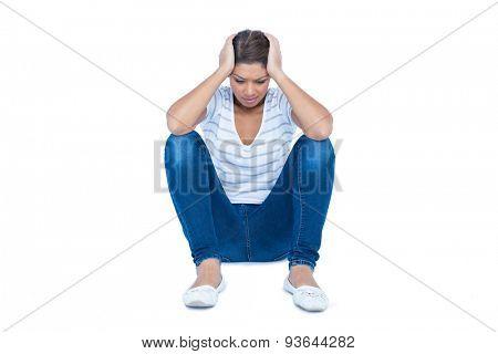 Pretty brunette sitting on floor with headache on white background