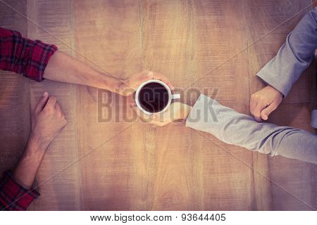 Upward view of two hands warming a cup of coffee