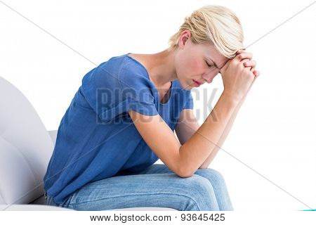 Thoughtful blonde woman sitting on the couch on white background