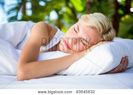Beautiful blonde woman lying outside on a sunny day