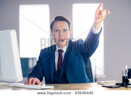 Angry businessman pointing and shouting in his office