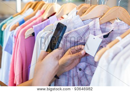 Woman scanning bar code with her mobile phone in clothes store