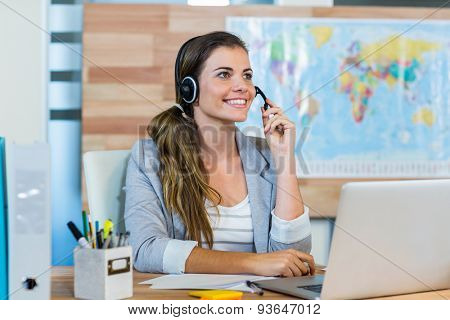 Pretty travel agent speaking to customer in the office