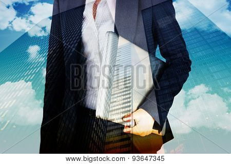 Businesswoman holding laptop against low angle view of skyscrapers