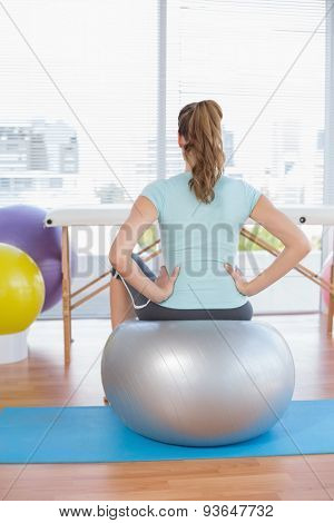 Woman sitting on exercise ball in fitness studio