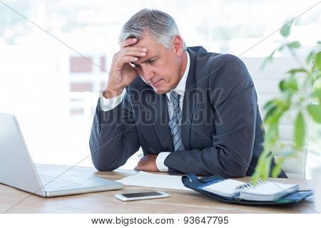 Worried businessman with head in one hand in his office