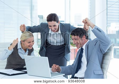 Cheerful business people cheering in front of laptop at office desk