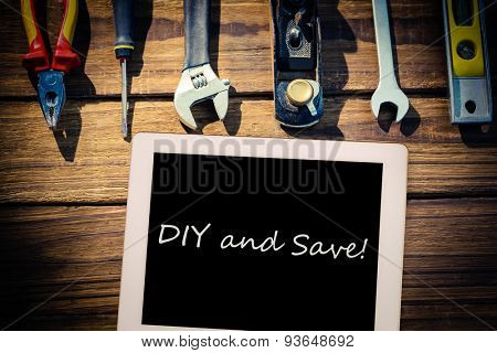 The word diy and save! and tablet pc against desk with tools