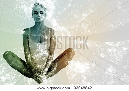 Toned woman doing the butterfly stretch against low angle view of tall trees