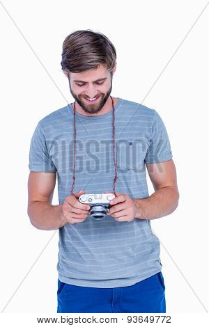Handsome man looking at his photo camera on white background
