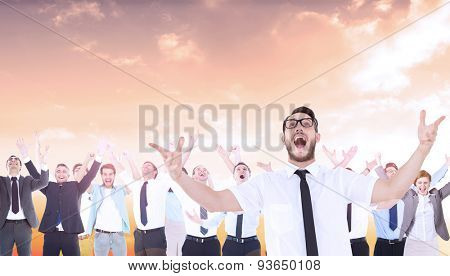 Geeky young businessman with arms out against beautiful orange and blue sky
