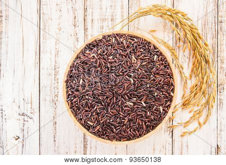 Raw Purple Rice Berry In Wooden Bowl On White Wooden Background