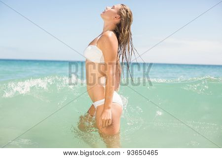 Pretty blonde bathing into the sea at the beach