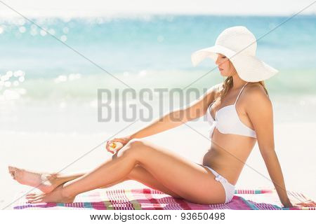 Pretty blonde woman putting sun tan lotion on her leg at the beach