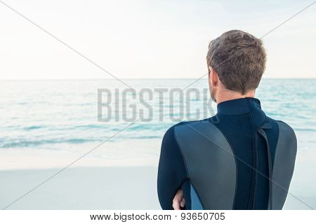 Man in wetsuit on a sunny day looking at sea