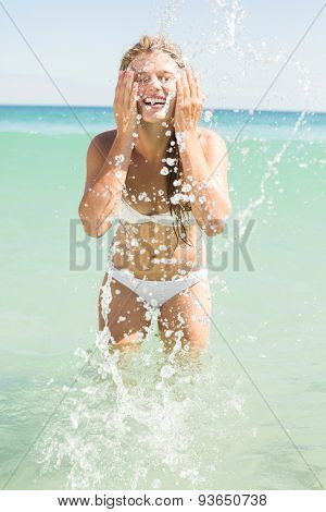Pretty blonde watering her face at the beach