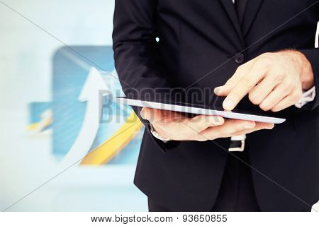 Mid section of a businessman touching digital tablet against digital blue background with screens including graphs
