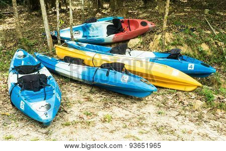Colorful kayaks on the riverbank for travel.
