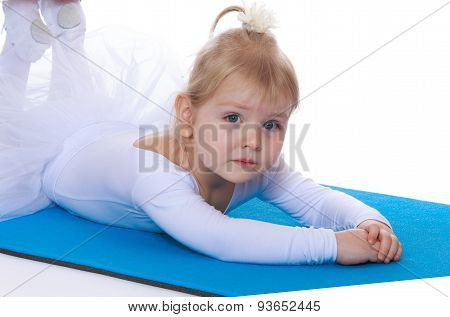 Little girl athlete in a white tracksuit lying on the floor,