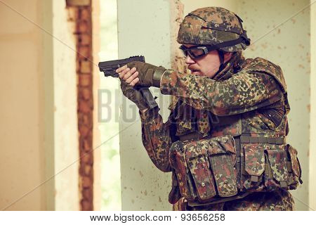 military. soldier with pistol in nato germany uniform with pistol indoord