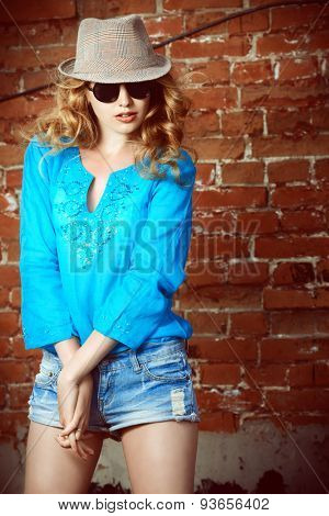 Lovely young woman in casual blouse and sunglasses outdoor. Fashion shot.