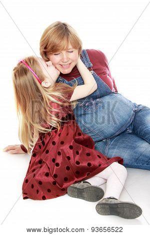 Little girl kisses his beloved pregnant mother