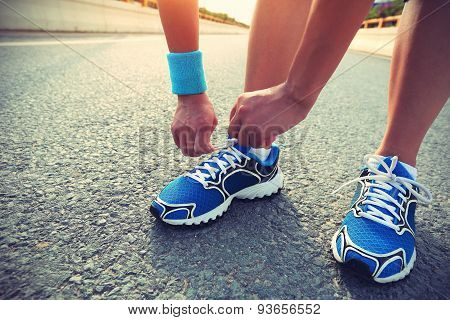 young woman runner hands tying shoelace on city road