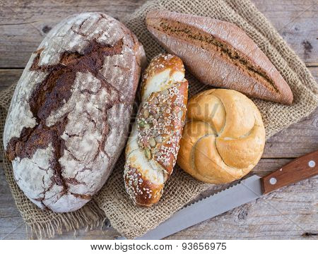 A loaf of dark bread and a small bread on the table