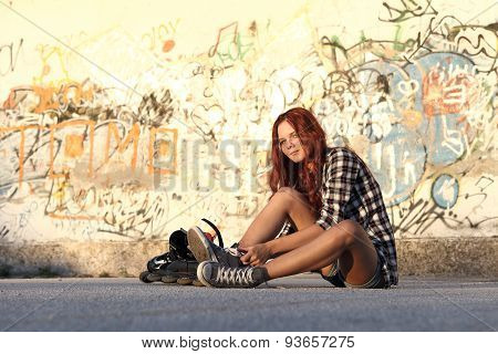 Sitting Girl With Roller Skates On urban Background