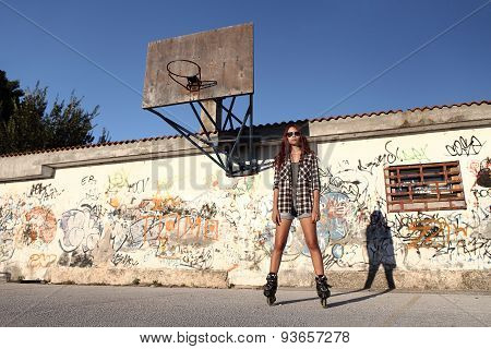 Girl With Roller Skates On urban Background And A Basketball Hoop