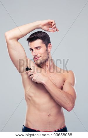 Handsome man shaving his armpit over gray background and looking at camera