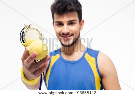 Happy sports man holding medal and tennis ball isolated on a white background. Focus on tennis ball