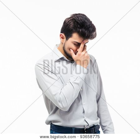 Upset young man covering his face with palm isolated on a white background
