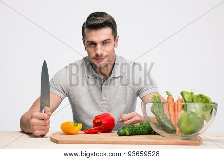 Happy man sitting at the table and preparing salad over gray background