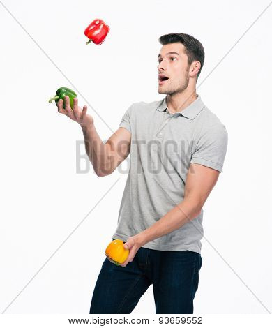 Happy young casual man juggling pepper isolated on a white background