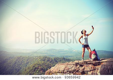 woman hiker taking photo with smart phone at mountain peakvintage effect