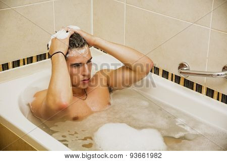 Handsome young man in bathtub at home having bath